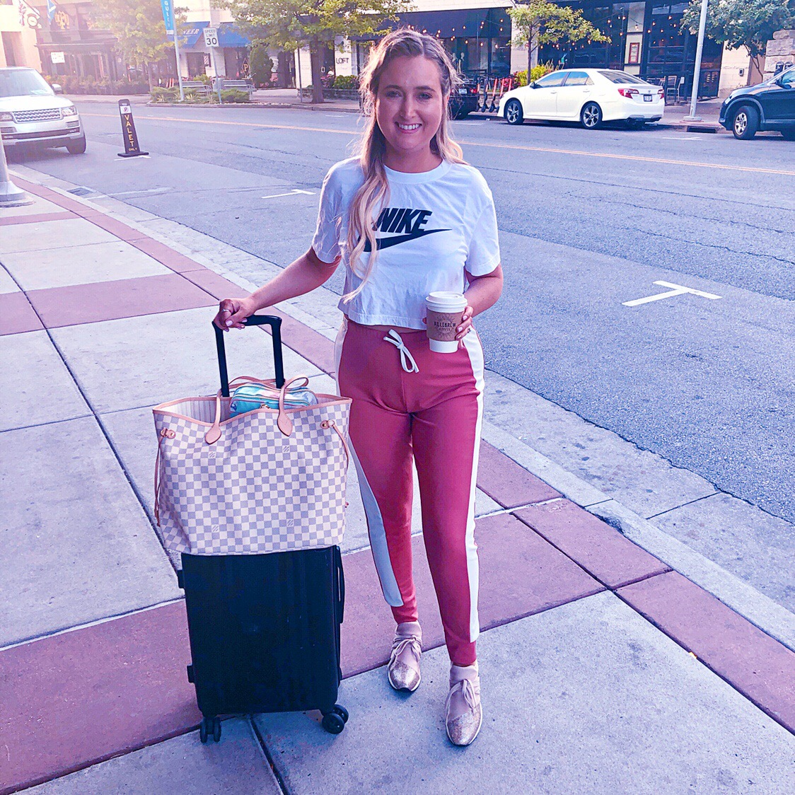 airport outfit, nashville airport outfit, jslides, j slides zorro sneakers, pink joggers, nike cropped top, calpak luggage, louis vuitton neverfull gm damier azur